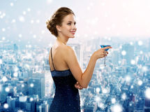 Smiling woman in evening dress holding cocktail Stock Image