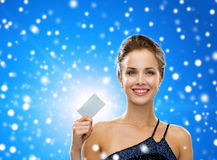 Smiling woman in evening dress holding credit card Royalty Free Stock Images