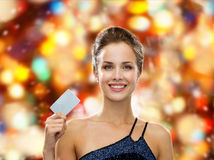 Smiling woman in evening dress holding credit card Stock Images