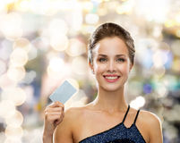 Smiling woman in evening dress holding credit card. Shopping, wealth, money, luxury and people concept - smiling woman in evening dress holding credit card over Royalty Free Stock Image