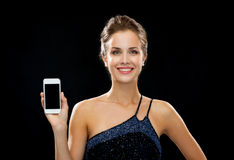 Smiling woman in evening dress holding smartphone Stock Image