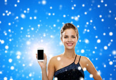 Smiling woman in evening dress holding smartphone. Technology, advertisement, winter holidays, christmas and people concept - smiling woman in evening dress with Stock Images