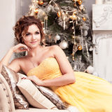 Smiling woman in evening dress  over christmas Stock Photo