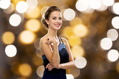 Smiling woman in evening dress and pearl earring. People, holidays, jewelry and luxury concept - smiling woman in evening dress and pearl earring over lights Stock Photos