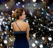 Smiling woman in evening dress. People, holidays, christmas and people concept - smiling woman in evening dress over snowy night city background from back Royalty Free Stock Photography