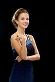 Smiling woman in evening dress. People, holidays and glamour concept - smiling woman in evening dress over black background Stock Photos