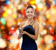 Smiling woman in evening dress with smartphone Royalty Free Stock Photo