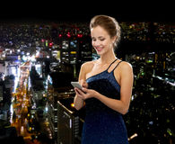 Smiling woman in evening dress with smartphone Stock Images