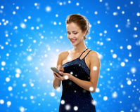 Smiling woman in evening dress with smartphone Stock Photo