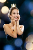 Smiling woman in evening dress wearing crown Stock Photo
