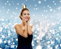 Smiling woman in evening dress wearing crown. People, holidays, royalty and christmas concept - smiling woman in evening dress wearing golden crown over snowy Royalty Free Stock Images