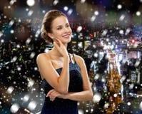 Smiling woman in evening dress wearing earrings Stock Photo