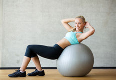 Smiling woman with exercise ball in gym Royalty Free Stock Photography