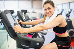 Smiling woman on the exercise bike Stock Photo