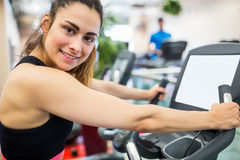 Smiling woman on the exercise bike Royalty Free Stock Image
