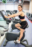 Smiling woman on the exercise bike. At the gym Stock Image