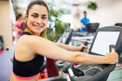 Smiling woman on the exercise bike. At the gym Stock Photography