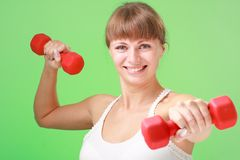 Smiling woman exercising with dumbbells Stock Image