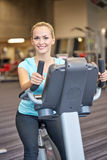 Smiling woman exercising on exercise bike in gym Stock Photo