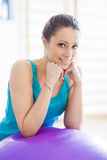 Smiling woman exercising at gym with fitness ball Stock Image