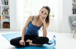 Smiling woman exercising at home on the floor. Smiling woman exercising at home, she is having a break and sitting on the floor, fitness and wellness concept royalty free stock photos