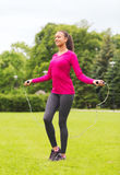 Smiling woman exercising with jump-rope outdoors Royalty Free Stock Images