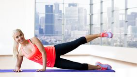Smiling woman exercising on mat over gym Stock Photography
