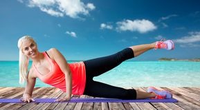 Smiling woman exercising on mat over sea Royalty Free Stock Photo