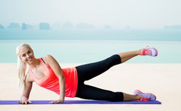 Smiling woman exercising on mat over sea and pool Royalty Free Stock Photography
