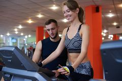 Smiling woman exercising with personal trainer on treadmill royalty free stock photography