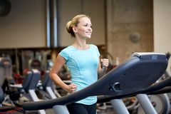 Smiling woman exercising on treadmill in gym. Sport, fitness, lifestyle, technology and people concept - smiling woman exercising on treadmill in gym Royalty Free Stock Images