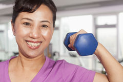 Smiling woman exercising with weights, arm raised, in the gym Stock Image