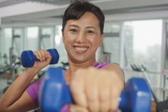 Smiling woman exercising with weights and looking at camera Royalty Free Stock Images