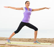 Smiling woman exercising yoga poses on beach Royalty Free Stock Photography