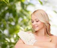 Smiling woman with exfoliation glove Royalty Free Stock Photos