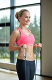 Smiling woman with expander in gym Stock Images