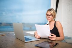 Female manager reading contract during work on net-book stock images