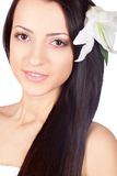 Smiling woman face portrait with lily in her hair Royalty Free Stock Image