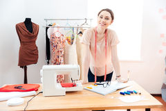 Smiling woman fashion designer standing and working in studio Stock Image