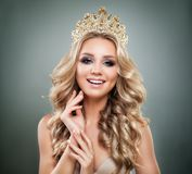 Smiling Woman Fashion Model with Makeup, Blonde Wavy Hair. And Golden Crown stock photo