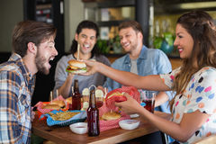 Smiling woman feeding burger to male friend Stock Photos