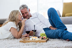 Smiling woman feeding food to man while lying on rug Royalty Free Stock Photography