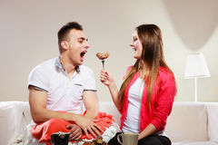 Smiling woman feeding happy man with cake. Royalty Free Stock Photos