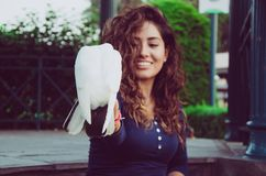 A smiling woman feeding a pigeon from her hand royalty free stock photography