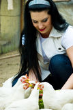 Smiling woman feeding poultry Royalty Free Stock Photography