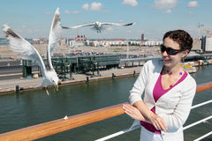 Smiling woman feeds seagulls on deck of ship Royalty Free Stock Images