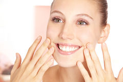 Smiling woman feeling pure skin Stock Image