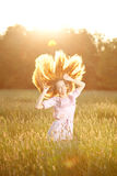 Smiling woman  in a field at sunset with flying hair Royalty Free Stock Photos