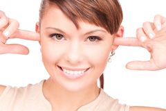 Smiling woman with fingers in ears Stock Photos