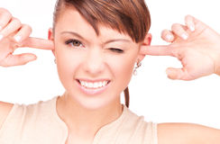 Smiling woman with fingers in ears. Picture of smiling woman with fingers in ears Royalty Free Stock Image